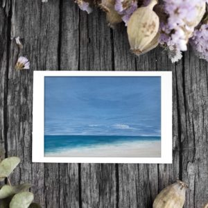Beach painting with cloudy sky with flowers on a wooden background