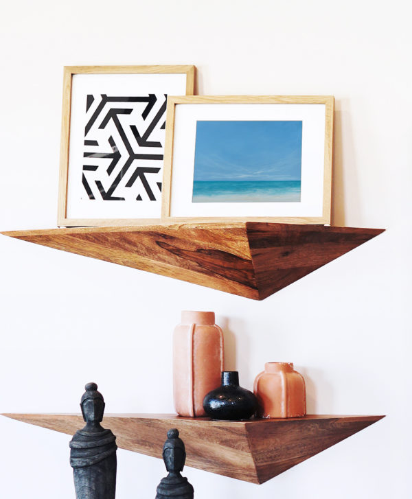 tropical beach painting in frame on shelf with artefacts