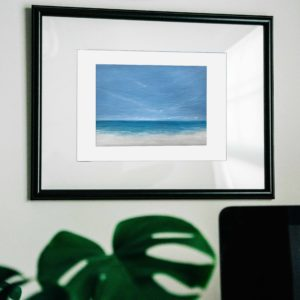 tropical beach painting in frame with monsterra plant