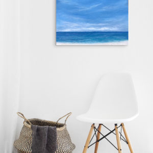 tropical beach painting in white room with chair