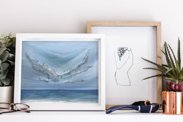 acrylic and mixed media painting in frame on shelf